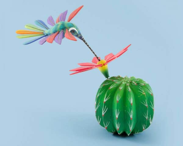 A wood carving with great balance, a colorful hummingbird eating from a round viznaga cactus flower. The hummingbird wings and tail, and the flower petals are detachable