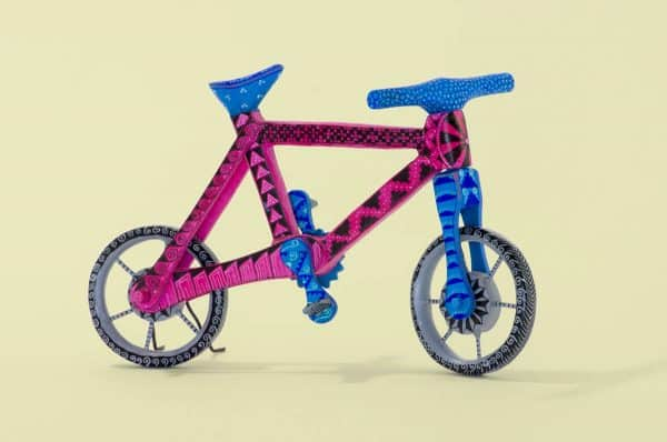 An original bicylce wood carving by artists Jesus & Roxana Hernandez.Painted in blue and magenta patterns, this piece features their signature style on the handlebars, which is easy to identify by the scale-like pattern in a sea of skilfully painted dots. It has spinning wheels and pedals. Extraordinary Mexican art from MexArt, London UK.