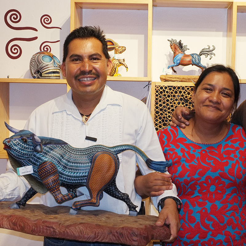 A portrait of mexican Artist Jacobo and Maria Angeles holding a handmade bull alebrije at their workshop in Oaxaca