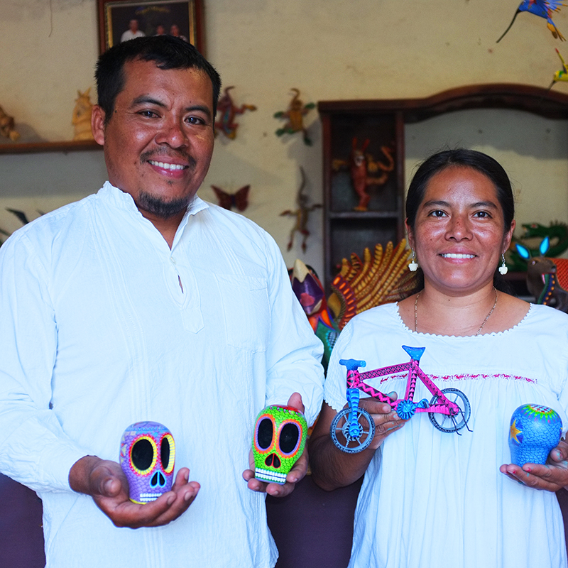 Jesus and Roxana mexican artisans holding colorful mexican skulls and award winner wooden pink bicycle