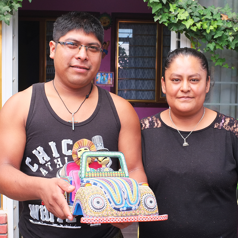 Portrair of mexican oaxacan artist Manuel prudencio and his wife holding a handmade car colorfully painted and with mobile parts