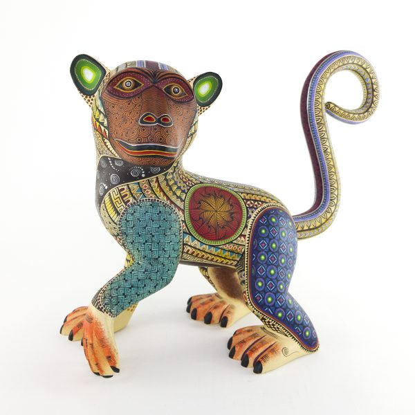 Beautiful smiley monkey alebrije painted in delicate patterns. Yellow body, brown face, blue legs and a detachable tail.