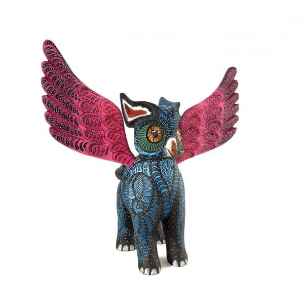 A surreal wood carving half owl half elephant, blue body with pink detachable wings with a very distinctive painting style