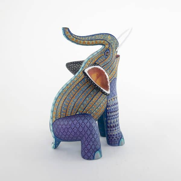 Cute elephant sitting and lifting up his trunk. Design in purple, yellow and blue. This piece has detachable tusks