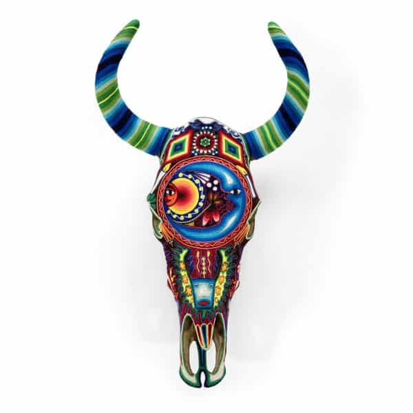 Large handmade huichol resin cow skull decorated with bright color yarn, glued with bee's wax with a design of a sun and a moon