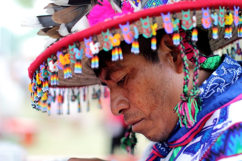 Mexican huichol artist with traditional hat decorated with beads and feathers
