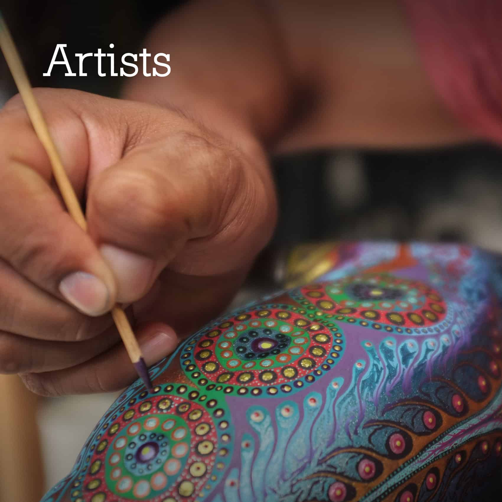 Close up oa the hand of a mexican artist delicately painting a wood alebrije with a stick